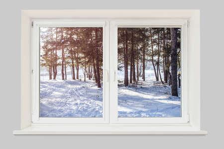Uitzicht vanuit het raam naar het winterbos verlicht door de zon Stockfoto