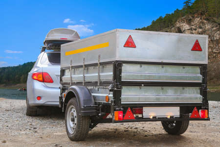 Car trailer and roof rack by the river Stockfoto