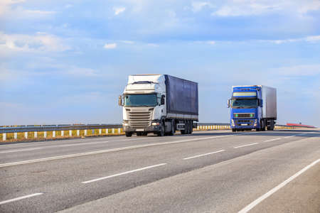 I camion vanno in autostrada di sera Archivio Fotografico