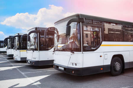 big tourist buses on parking on the background of cloudy sky