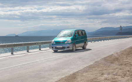 Minivan moves on the highway along the sea coast