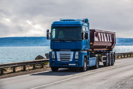 Truck is moving along the coastal road 写真素材
