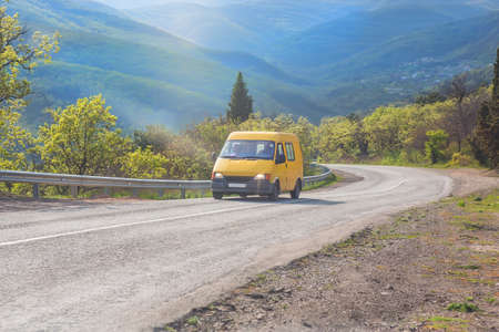 Yellow minibus is moving along the road in the highlands. Stock Photo