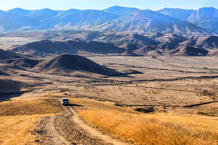 mountain landscape with an SUV moving along a dirt road