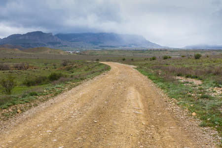 Dirt road to the open mountain range under thunder clouds