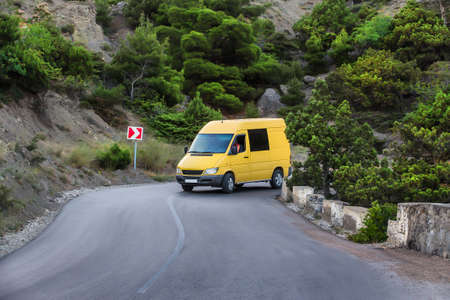 Minibus moves along a winding mountain road 写真素材