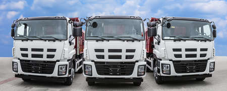 Three large trucks front view on the road against the sky Imagens