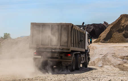 dump truck on a dusty road delivers crushed stone to the storage of building road materials Stock Photo