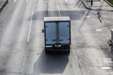 Truck goes on a city street. Cargo delivery Stock Photo