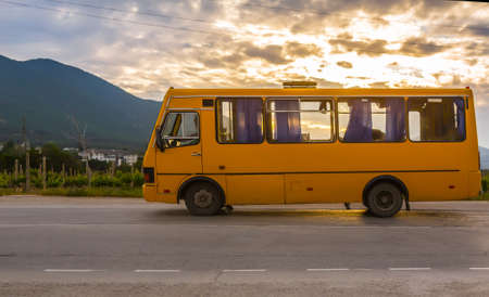 bus goes along the road along the mountains at sunset