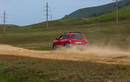 SUV moving on a dirt dusty road in a hilly area