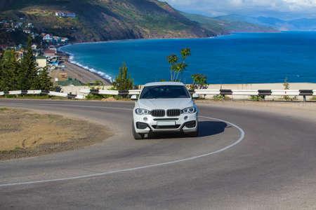 Car Moves along a winding road along the sea shore. Reklamní fotografie
