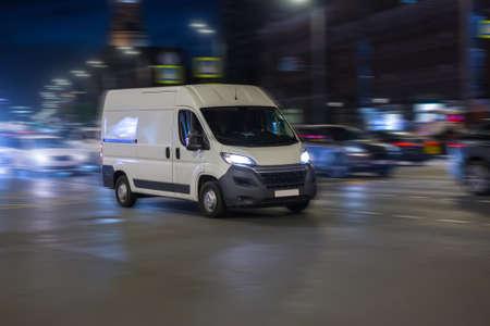 Minibus Moves at Night Along City Ctreet Stock Photo