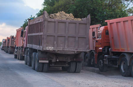 convoy of dumped trucks on the road
