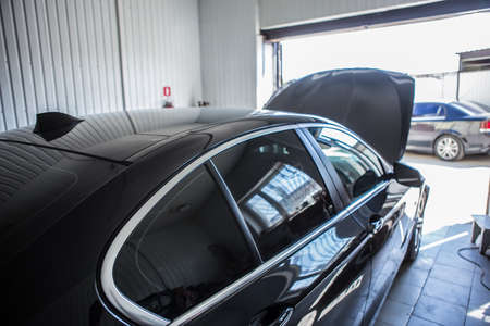black luxury car under repair in car service