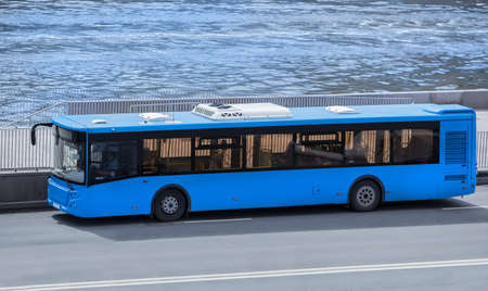 Bus Moves Along the River Embankment in the City