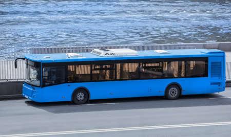 Le bus se déplace le long de la berge de la rivière dans la ville