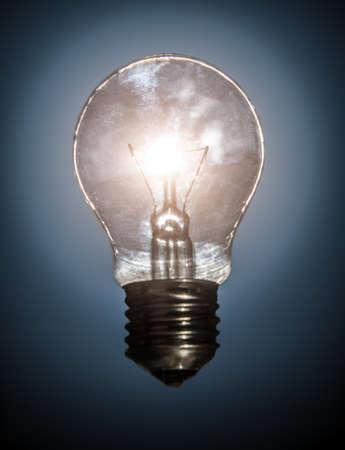 glowing light bulb on dark background in a halo of light 免版税图像