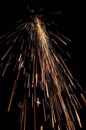 bright sparks of metal against dark background