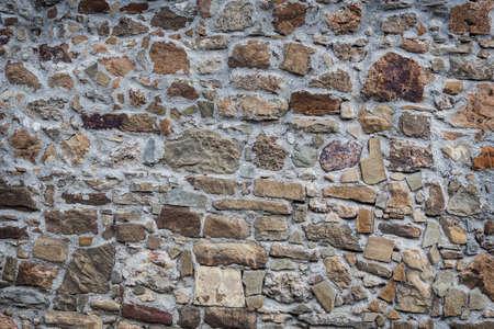 Background.Stone Wand aus rauen, unverarbeiteten Steinen.