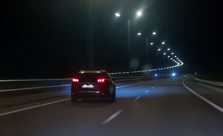 Car moves at high speed on a suburban highway at night.