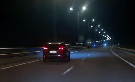 La voiture se déplace à grande vitesse sur une autoroute de banlieue la nuit.