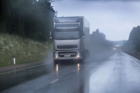 truck moving in rain and fog on a country road