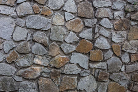 Background.Stone wall of rough unprocessed stones. 写真素材