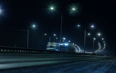 Truck traffic on a winter highway at night