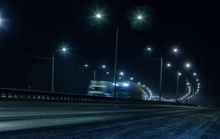 Vrachtwagenverkeer op een wintersnelweg 's nachts