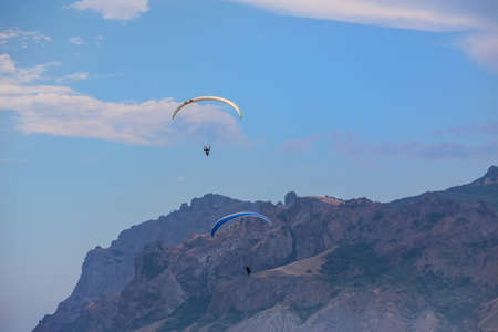 Parachutists on paragliders fly in the sky over the mountains