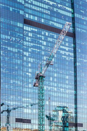 Construction cranes in front of the glass facades of modern office buildings