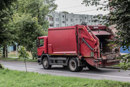 Garbage truck moving on a city street near buildings