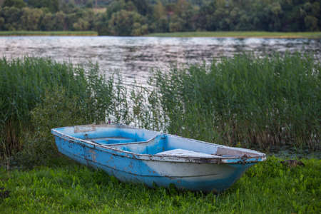 Old fishing boat on the grass by the river in summer Stockfoto