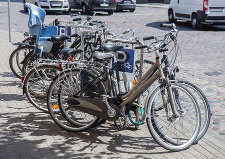 Bicicletas en un parque de bicicletas en la acera junto a la carretera Foto de archivo