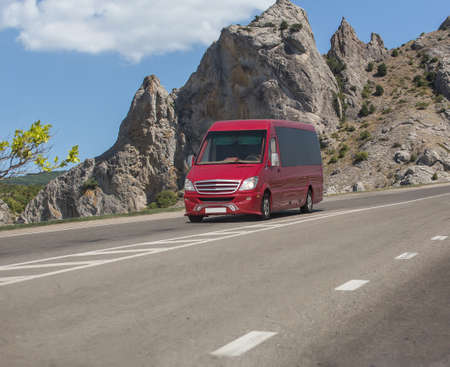 Red minibus moves on a road in the mountains on a summer day Reklamní fotografie