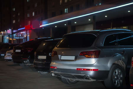 row of cars at night in the parking lot at the store Stockfoto