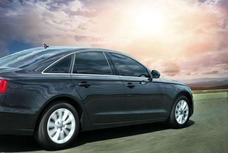 Black prestigious car rides on the highway against the sky against the sun