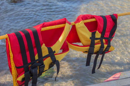 Life jackets on a pier guard near the water
