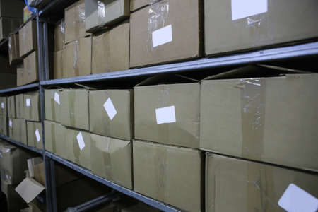 Cardboard rectangular boxes on warehouse shelves