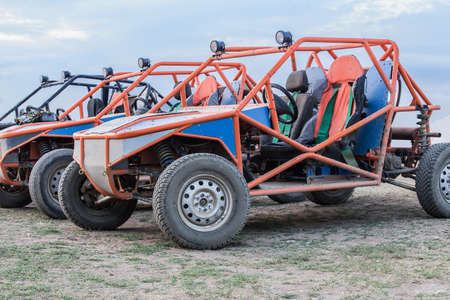Three buggies after off-road driving on a field against the sky