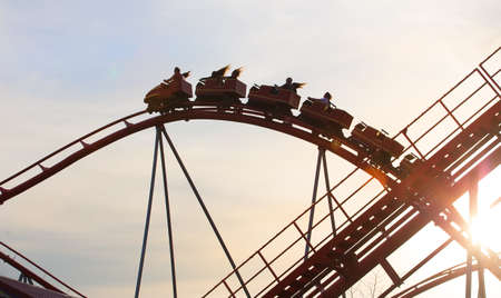 Roller coaster ride against the sky at sunset