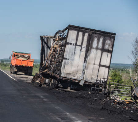 Burnt truck on the side of a country highway