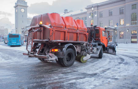 Snowplow removes snow on a town square.