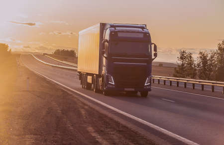 truck moves along a suburban highway at sunset lit by the sun Foto de archivo