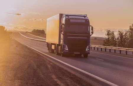 le camion se déplace le long d'une autoroute de banlieue au coucher du soleil éclairé par le soleil Banque d'images