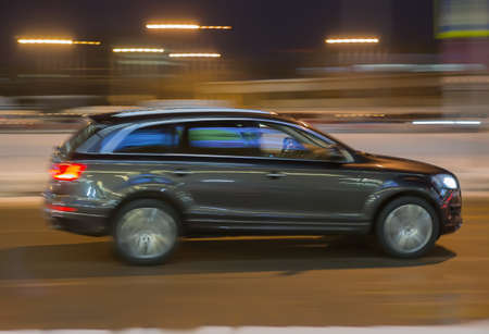 SUV moves through the night city in winter. Motion blur.
