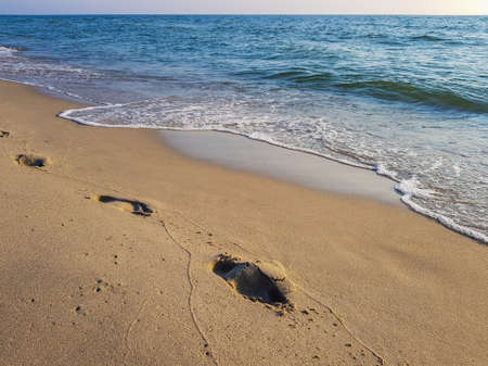 Footprints of a man walking along the sand at the water's edge on the sea beach Stok Fotoğraf