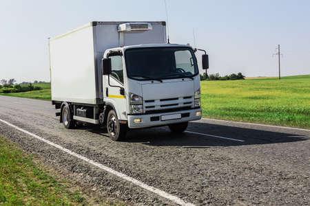 LKW fährt auf einer Landstraße entlang eines Feldes
