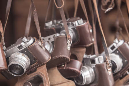 Vintage analog cameras in leather cases close-up.